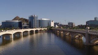 DX0002_142_014 - 5.7K stock footage aerial video descend between two bridges with view of modern office buildings in Tempe, Arizona