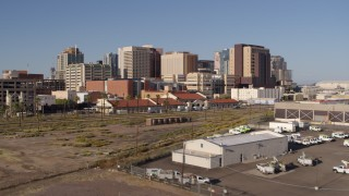 DX0002_142_021 - 5.7K stock footage aerial video ascend and approach the city's skyline behind train station in Downtown Phoenix, Arizona