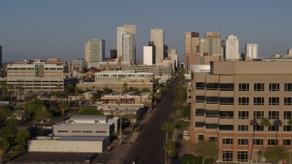 DX0002_143_007 - 5.7K stock footage aerial video the city's skyline at sunset while flying by street to reveal state office building in Downtown Phoenix, Arizona