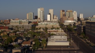 DX0002_143_012 - 5.7K stock footage aerial video follow Adams Street toward city's skyline at sunset in Downtown Phoenix, Arizona
