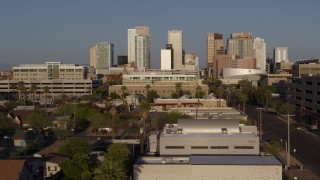 DX0002_143_013 - 5.7K stock footage aerial video follow Adams Street toward city's skyline at sunset in Downtown Phoenix, Arizona