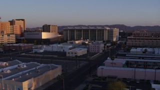DX0002_143_040 - 5.7K stock footage aerial video of passing a performing arts theater, courthouse and TV station at sunset, Downtown Phoenix, Arizona