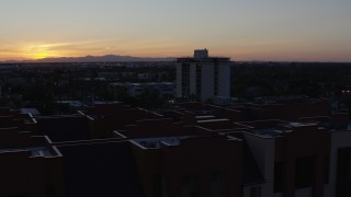 DX0002_143_053 - 5.7K stock footage aerial video orbit apartment complex with the sun setting behind distant mountains, seen from Phoenix, Arizona