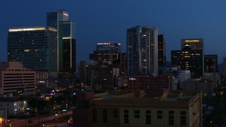 DX0002_143_062 - 5.7K stock footage aerial video reverse view of high-rise office buildings, reveal Westward Ho building at twilight, Downtown Phoenix, Arizona