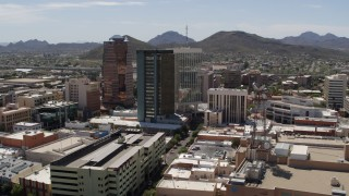 DX0002_144_002 - 5.7K stock footage aerial video of ascending past office high-rises, with Sentinel Peak in the distance, Downtown Tucson, Arizona