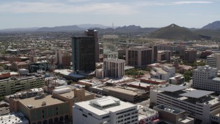 DX0002_144_009 - 5.7K stock footage aerial video ascend past courthouse to orbit office high-rises and reveal Sentinel Peak, Downtown Tucson, Arizona