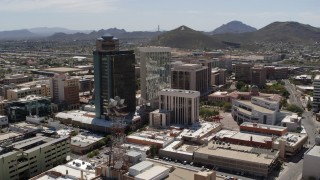 DX0002_144_010 - 5.7K stock footage aerial video of orbiting three downtown office high-rises with Sentinel Peak in the distance, Downtown Tucson, Arizona