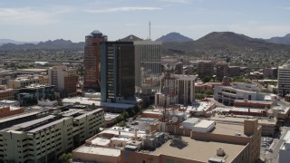 "DX0002_144_013 - 5.7K stock footage aerial video of circling high-rise office buildings, ""A"" Mountain (Sentinel Peak) in the distance, Downtown Tucson, Arizona"