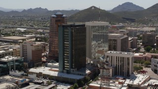 "DX0002_144_016 - 5.7K stock footage aerial video orbiting three high-rise office towers, revealing ""A"" Mountain (Sentinel Peak), Downtown Tucson, Arizona"