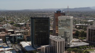 DX0002_144_021 - 5.7K stock footage aerial video orbiting office buildings with Sentinel Peak in the background, Downtown Tucson, Arizona