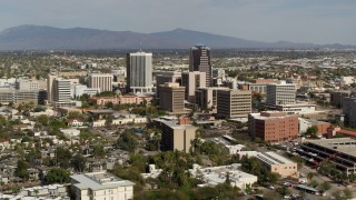 DX0002_144_035 - 5.7K stock footage aerial video reverse view of tall office high-rises surrounded by city buildings in Downtown Tucson, Arizona