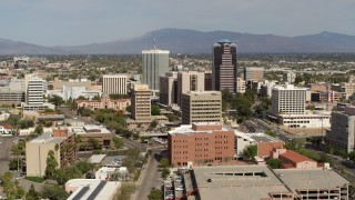 DX0002_144_038 - 5.7K stock footage aerial video ascend and fly away from tall office high-rises surrounded by city buildings in Downtown Tucson, Arizona