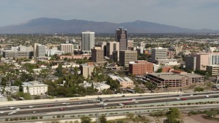DX0002_144_039 - 5.7K stock footage aerial video reverse view of tall office high-rises and city buildings, seen from I-10, Downtown Tucson, Arizona