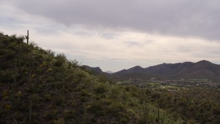 DX0002_145_002 - 5.7K stock footage aerial video fly over small peak with cactus plants, reveals homes and golf course in Tucson, Arizona