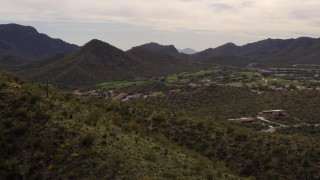 DX0002_145_003 - 5.7K stock footage aerial video fly away from homes and golf course, reveal mountain slope with cactus in Tucson, Arizona