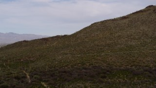 DX0002_145_014 - 5.7K stock footage aerial video of flying away from cactus and vegetation on Sentinel Peak in Tucson, Arizona