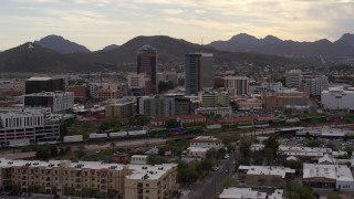 DX0002_145_036 - 5.7K stock footage aerial video orbit office towers as a train passes, with Sentinel Peak in the background, Downtown Tucson, Arizona