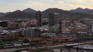 DX0002_145_038 - 5.7K stock footage aerial video orbit office towers as a train passes, with Sentinel Peak in the background, Downtown Tucson, Arizona