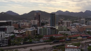 DX0002_145_039 - 5.7K stock footage aerial video wide orbit of office towers as a train passes, with Sentinel Peak in the distance, Downtown Tucson, Arizona