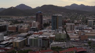 DX0002_145_041 - 5.7K stock footage aerial video ascend while flying away from office towers, Sentinel Peak in distance, Downtown Tucson, Arizona