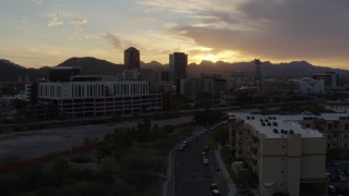 DX0002_146_030 - 5.7K stock footage aerial video flying away from tall office towers at sunset in Downtown Tucson, Arizona