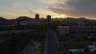 DX0002_146_031 - 5.7K stock footage aerial video approaching tall office towers and city buildings at sunset in Downtown Tucson, Arizona