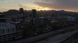 DX0002_146_032 - 5.7K stock footage aerial video flying by tall office towers and city buildings at sunset in Downtown Tucson, Arizona