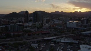 DX0002_146_033 - 5.7K stock footage aerial video passing tall office towers and city buildings with view of Sentinel Peak at sunset in Downtown Tucson, Arizona
