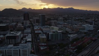 DX0002_146_034 - 5.7K stock footage aerial video a view of tall office towers and city buildings with view of setting sun in Downtown Tucson, Arizona