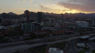 DX0002_146_035 - 5.7K stock footage aerial video flying by high-rise office towers and city buildings with view of setting sun in Downtown Tucson, Arizona