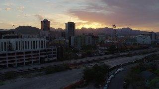 DX0002_146_037 - 5.7K stock footage aerial video fly low by railroad tracks and away from high-rise office towers, and setting sun in Downtown Tucson, Arizona