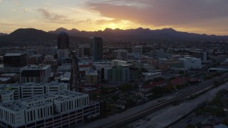 DX0002_146_038 - 5.7K stock footage aerial video ascend by railroad tracks toward high-rise office towers and setting sun in Downtown Tucson, Arizona