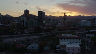 DX0002_146_044 - 5.7K stock footage aerial video pass railroad tracks while focused on high-rise office towers at sunset in Downtown Tucson, Arizona