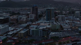 DX0002_147_005 - 5.7K stock footage aerial video flying by high-rise office towers at sunset with Sentinel Peak in distance, Downtown Tucson, Arizona