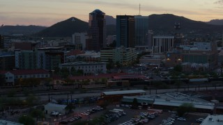 DX0002_147_006 - 5.7K stock footage aerial video passing high-rise office towers at sunset with Sentinel Peak in distance, Downtown Tucson, Arizona