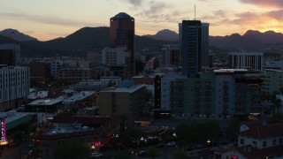 DX0002_147_009 - 5.7K stock footage aerial video approach and orbit high-rise office towers at sunset with mountains in distance, Downtown Tucson, Arizona