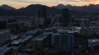 DX0002_147_010 - 5.7K stock footage aerial video reverse view of office towers at sunset with mountains in distance, Downtown Tucson, Arizona