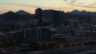 DX0002_147_013 - 5.7K stock footage aerial video pass by office towers at sunset with mountains in background, Downtown Tucson, Arizona