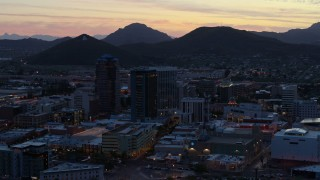 DX0002_147_019 - 5.7K stock footage aerial video of passing tall office towers at sunset, Sentinel Peak in the distance, Downtown Tucson, Arizona