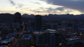 DX0002_147_024 - 5.7K stock footage aerial video descend while focused on tall office towers at sunset, Downtown Tucson, Arizona
