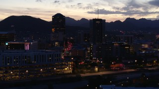 DX0002_147_030 - 5.7K stock footage aerial video ascend and approach tall office towers and Congress Street at twilight, Downtown Tucson, Arizona