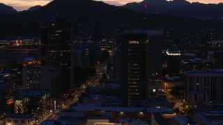 DX0002_147_033 - 5.7K stock footage aerial video circling tall office towers and reveal Congress Street at twilight, Downtown Tucson, Arizona