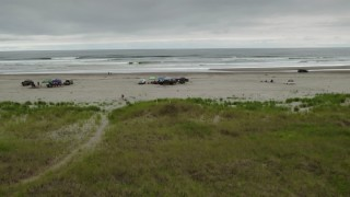 DX0002_148_004 - 4K stock footage aerial video approach and ascend near groups of people on the beach in Long Beach, Washington