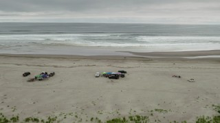 DX0002_148_014 - 4K stock footage aerial video fly away from people on the beach and ocean in Long Beach, Washington