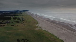 DX0002_148_023 - 4K stock footage aerial video of a reverse view of groups of beach-goers near the ocean in Long Beach, Washington