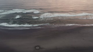 DX0002_148_024 - 4K stock footage aerial video of flying over the beach and ocean waves at sunset in Long Beach, Washington