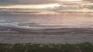 DX0002_148_026 - 4K stock footage aerial video of flying away from beach and ocean waves, tilt to focus on clouds at sunset in Long Beach, Washington
