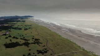 DX0002_148_028 - 4K stock footage aerial video approach the beach and ocean waves at sunset in Long Beach, Washington