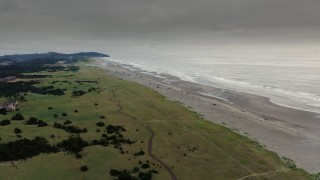 DX0002_148_029 - 4K stock footage aerial video fly away from the beach and ocean waves at sunset in Long Beach, Washington
