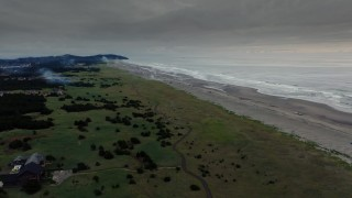 DX0002_148_036 - 4K stock footage aerial video fly toward the beach as fireworks go off at sunset in Long Beach, Washington